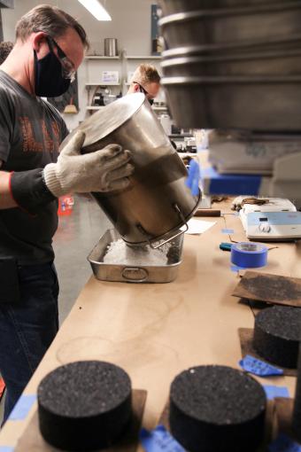 Lab staff prepare plastic waste pavement mixture for testing.