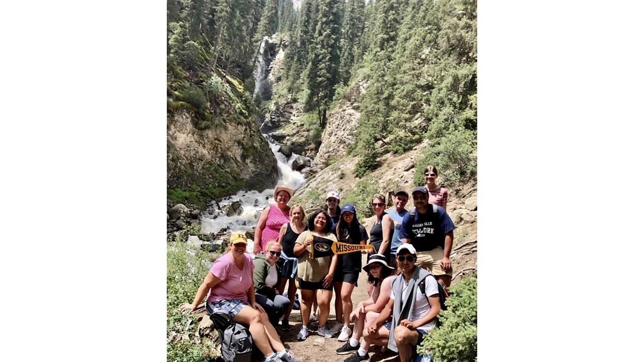 a group of students and faculty in front of a waterfall