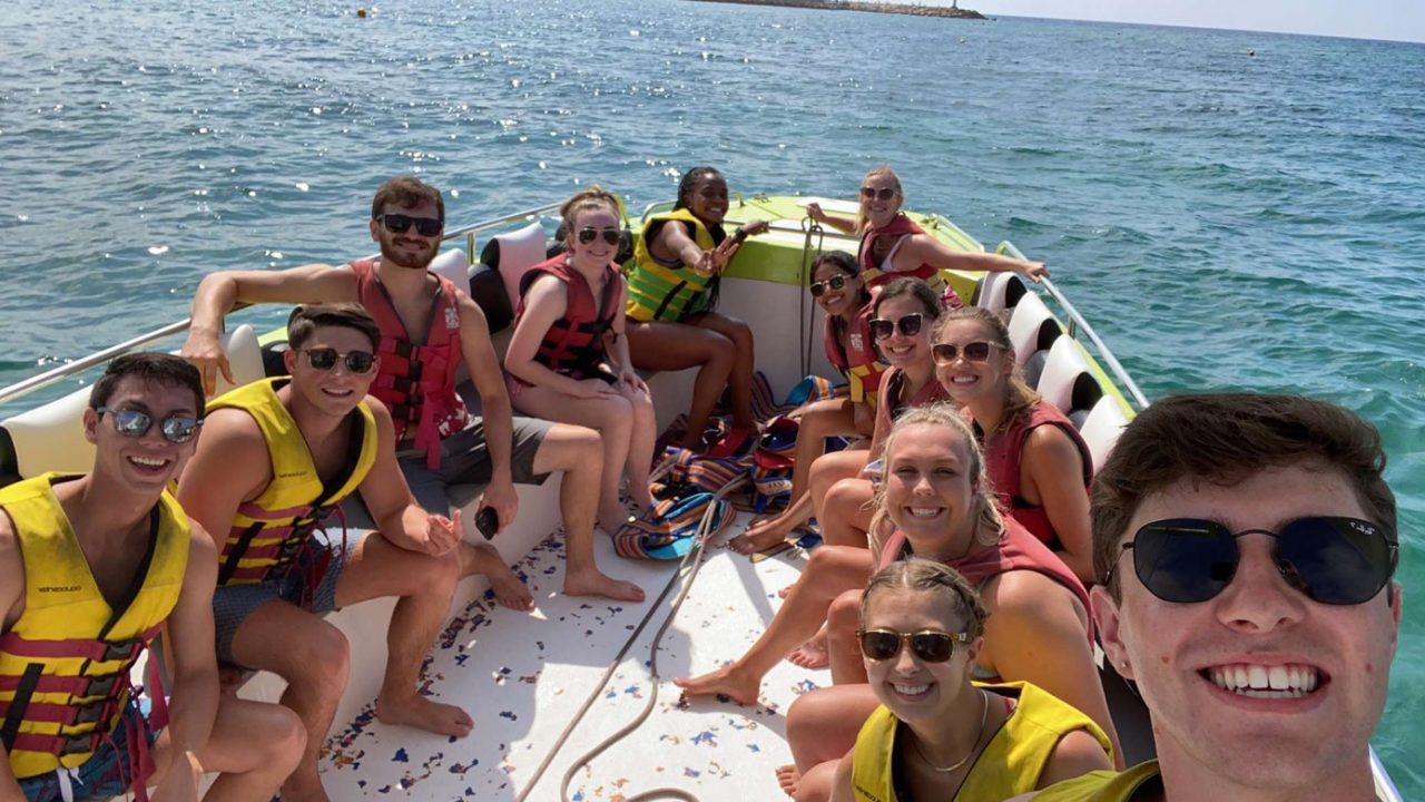 students smile on a boat in the ocean