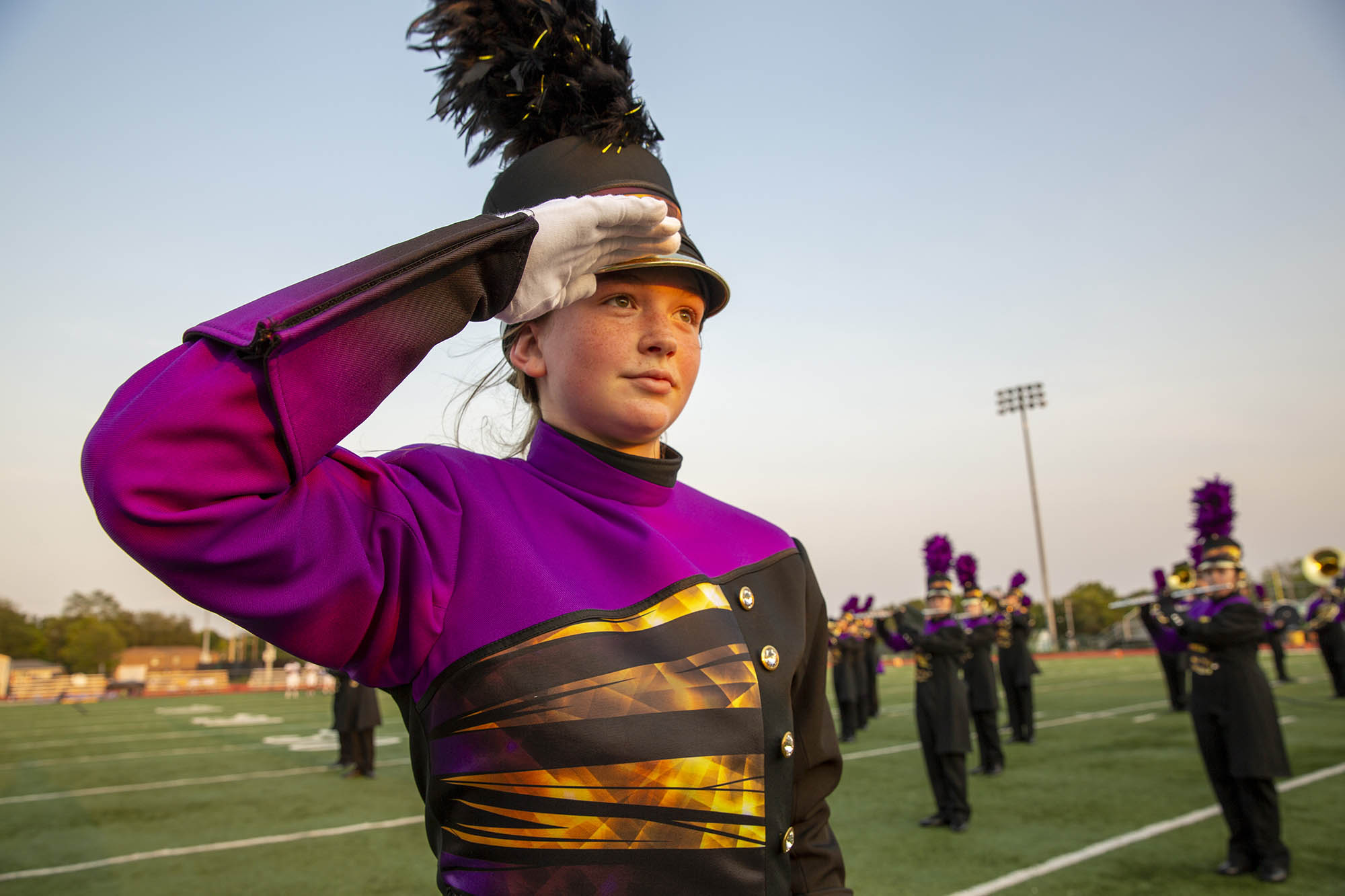 a student in a marching uniform salutes