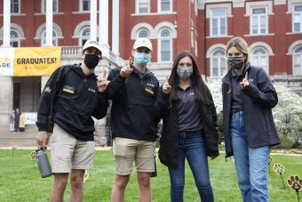 four students in front of jesse hall in AASB jackets and face coverings