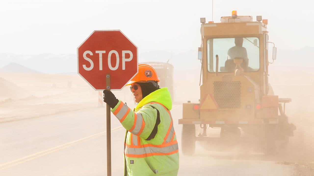 a woman with a stop sign in a work zone