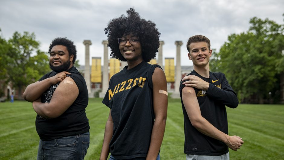 three students in front of the columns with bandaids on their upper arm