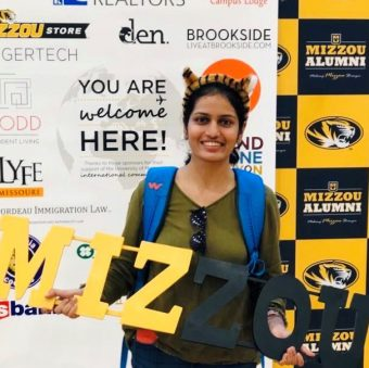 photo of a student with a mizzou sign smiling