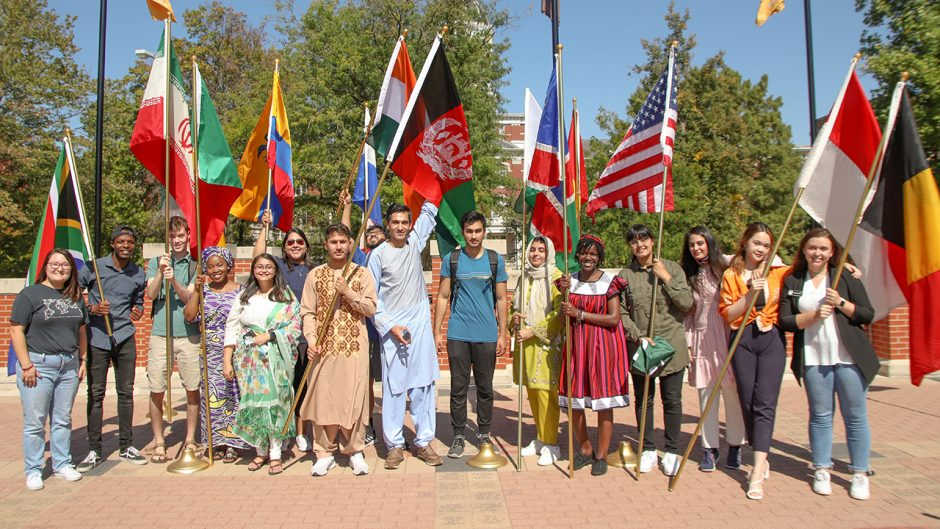 group of international students pose for a photo holding their countries' flag