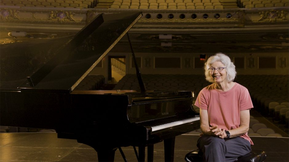 lucy urlacher sits at a piano smiling