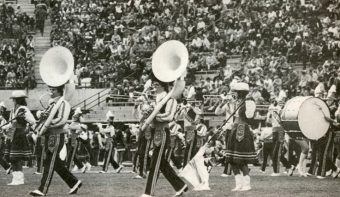 black and white photo from the 80s of a marching band playing on faurot field