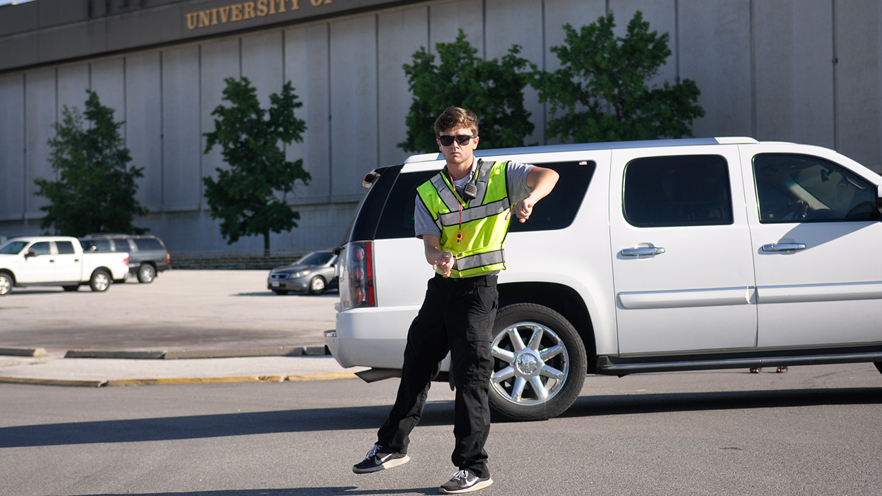 This is an image of a student volunteer directing traffic.