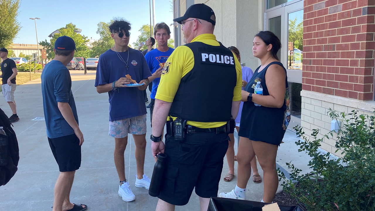 This is an image of a police officer talking to students.