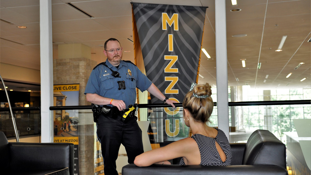 This is an image of a police officer talking to an adult.