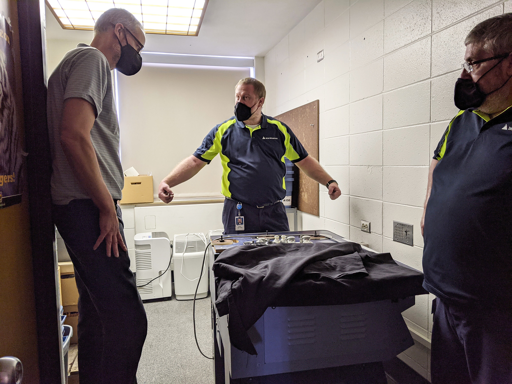 three men discuss moving a large imaging table