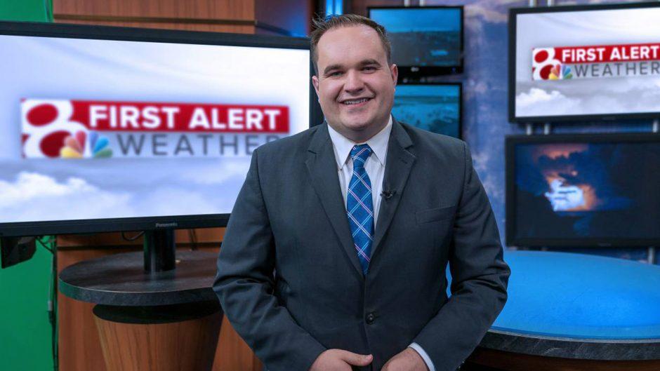 man smiling inside a tv station