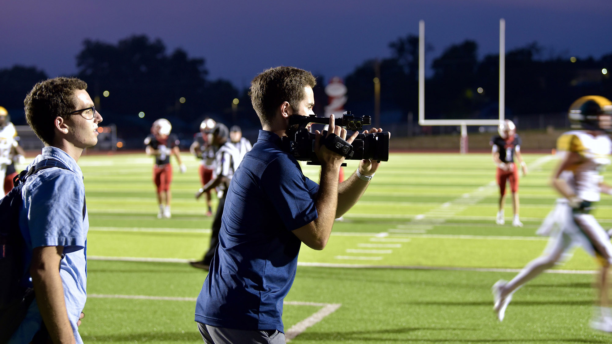 a student records video during a football game