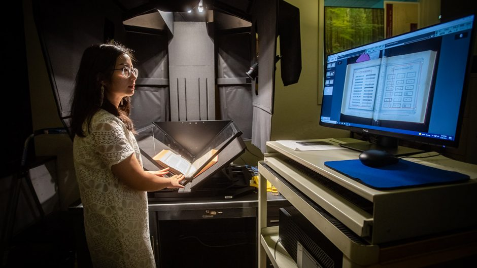 a woman scans an old book onto a computer
