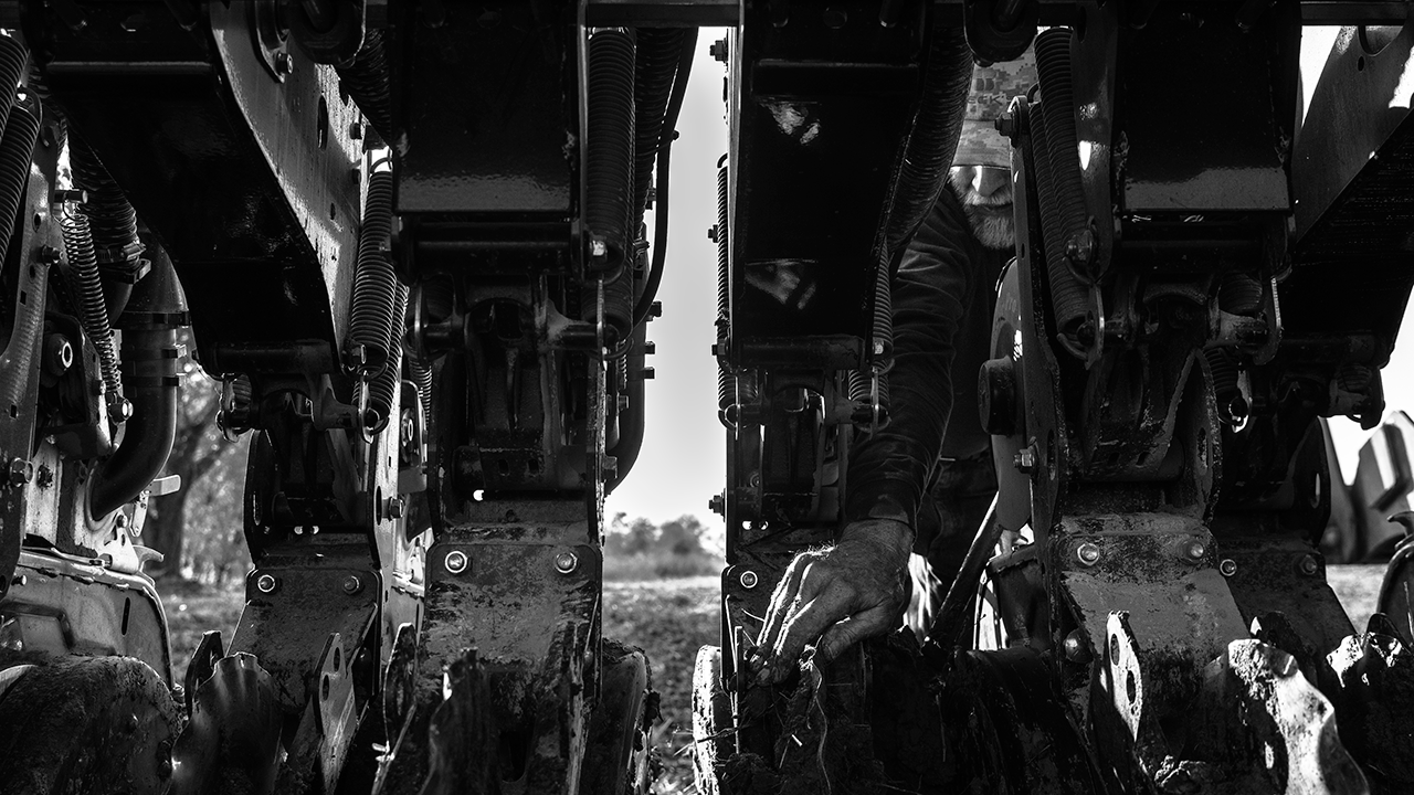 This is a picture submitted to CPOY of a man sticking his hand into farming equipment.