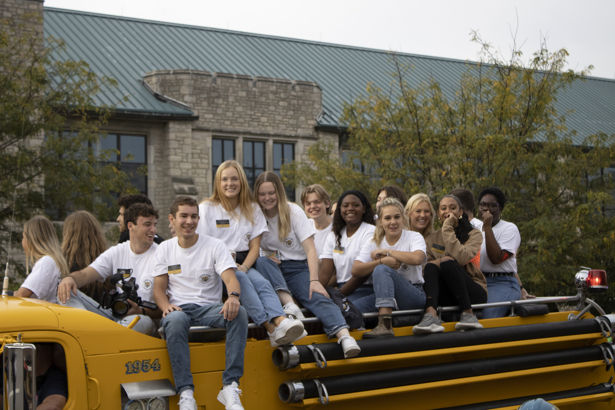 homecoming steering committee members ride in a fire truck and smile