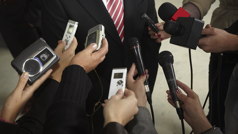 This is a photo of a person speaking with media members.